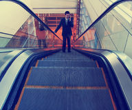A businessman riding an escalator toned with a retro vintage ins Stock Photography