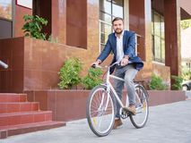 Businessman is riding his white bike down the street. Cheerful young man with a beard, in a good suit, a businessman is riding his white bike down the street Royalty Free Stock Photos