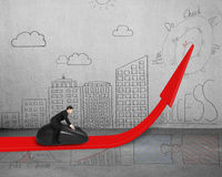 Businessman riding mouse on red arrow with doodles on wall Stock Photo
