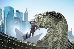 The businessman riding paper boat in dollar sea stock photography