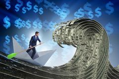 The businessman riding paper boat in dollar sea stock images