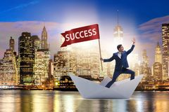 The businessman riding paper boat ship in success concept Stock Photo
