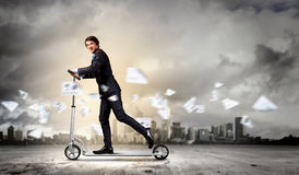 Businessman riding scooter Royalty Free Stock Photography