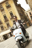 Businessman Riding Scooter Through Town Stock Photography