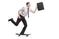 Businessman riding a skateboard Stock Images