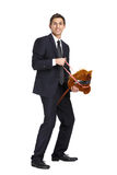 Businessman riding the toy horse Stock Images