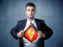 Businessman ripping off shirt and idea light bulb appears Royalty Free Stock Photo