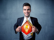 Businessman ripping off shirt and idea light bulb appears Stock Photography