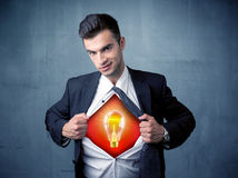 Businessman ripping off shirt and idea light bulb appears Stock Images