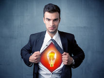 Businessman ripping off shirt and idea light bulb appears Royalty Free Stock Photos