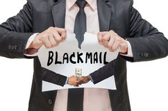 Businessman ripping up the BLACKMAIL  sign with receiving the money. Businessman ripping up the BLACKMAIL sign with receiving the money offered between two Royalty Free Stock Photography