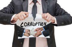 Businessman ripping up the CORRUPTION sign with receiving Stock Images