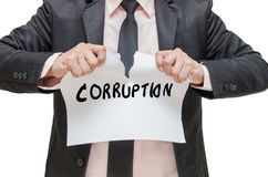 Businessman ripping up the CORRUPTION sign on white background Royalty Free Stock Image
