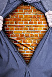 Hard As Bricks. A businessman rips open his shirt and shows how tough he is by revealing a brick wall beneath printed on a t-shirt Royalty Free Stock Photography