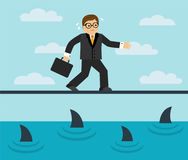Businessman risks and fears. Businessman risks and goes on a tightrope over the sea full of sharks Royalty Free Stock Photo