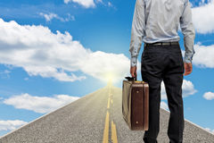 Businessman on the road to future. Businessman going to the future with suitcase on sunny day Royalty Free Stock Photo