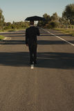 Businessman on the road with umbrella Royalty Free Stock Images