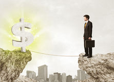 Businessman on rock mountain with a dollar mark Royalty Free Stock Photography