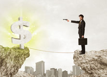 Businessman on rock mountain with a dollar mark Royalty Free Stock Photo