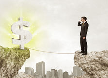 Businessman on rock mountain with a dollar mark Stock Photo