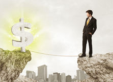 Businessman on rock mountain with a dollar mark Stock Photos