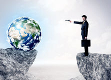 Businessman on rock mountain with a globe Stock Photos