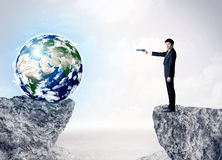 Businessman on rock mountain with a globe Royalty Free Stock Photo