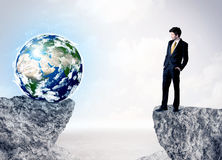 Businessman on rock mountain with a globe Stock Image