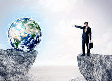 Businessman on rock mountain with a globe Stock Photo