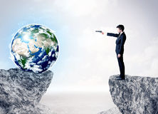 Businessman on rock mountain with a globe Royalty Free Stock Photos