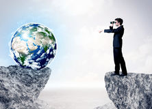 Businessman on rock mountain with a globe Stock Images
