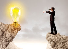 Businessman on rock mountain with idea bulb Royalty Free Stock Photos