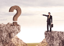 Businessman on rock mountain with a question mark Stock Photography