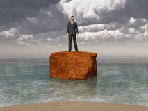 Businessman on a rock in the surf Stock Photos