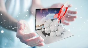 Businessman with rocket launching from a laptop 3D rendering. Businessman on blurred background with rocket launching from a laptop 3D rendering Stock Photos