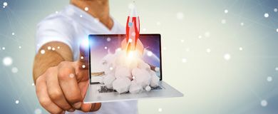 Businessman with rocket launching from a laptop 3D rendering. Businessman on blurred background with rocket launching from a laptop 3D rendering Stock Photo