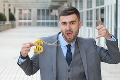 Businessman rocking golden necklace with dollar sign.  stock photos