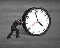Businessman rolling clock Royalty Free Stock Photos