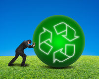 Businessman rolling large ball with recycling symbol on green fr. Esh meadow and blue sky background Stock Image