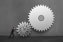 Businessman rolling large concrete gears with clock drawing in c Royalty Free Stock Images
