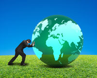 Businessman rolling large green ball with global map on it isola. Businessman rolling large green ball with global map on it with green meadow and clear blue sky Royalty Free Stock Photography
