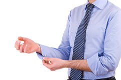 Businessman rolling up his shirt sleeves. Royalty Free Stock Photography
