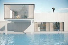 Businessman on roof of house. Businessman talking on phone on the roof of luxurious house exterior with swimming pool . 3D Rendering Stock Photography