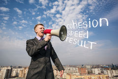 Businessman on the roof with megaphone Stock Photo
