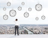 Businessman on the roof. Businessman standing with left hand on the head on the roof of a business centre and looking at Paris. Pocket watches hovering from Royalty Free Stock Image