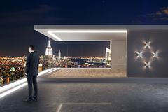 Businessman on rooftop. Young businessman standing on modern rooftop with penthouse and night New York city view royalty free stock photos