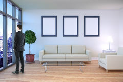 Businessman in room with frames. Thoughtful businessman looking out of window in living room interior with night city view, furniture and blank picture frames on Stock Photos
