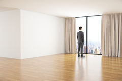 Businessman in room. Spacious clean room interior with wooden floor, concrete walls and businessman looking out of window with curtains and city view. Mock up Stock Photos