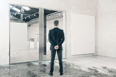 Businessman in room with whiteboard. Back view of young businessman in grungy interior with glass doors and empty whiteboard. Mock up, 3D Rendering royalty free stock photography