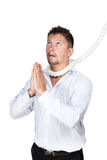 Businessman with a rope around his neck prays Stock Images